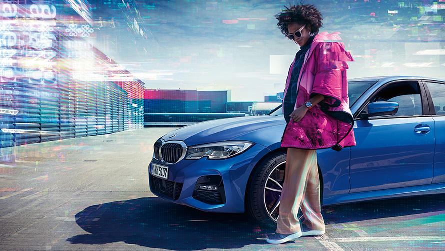 Стоп-кадр седана BMW 3 серии, вид сбоку с поворотом в три четверти, на открытой парковочной площадке, позади женщины на фоне городского пейзажа.