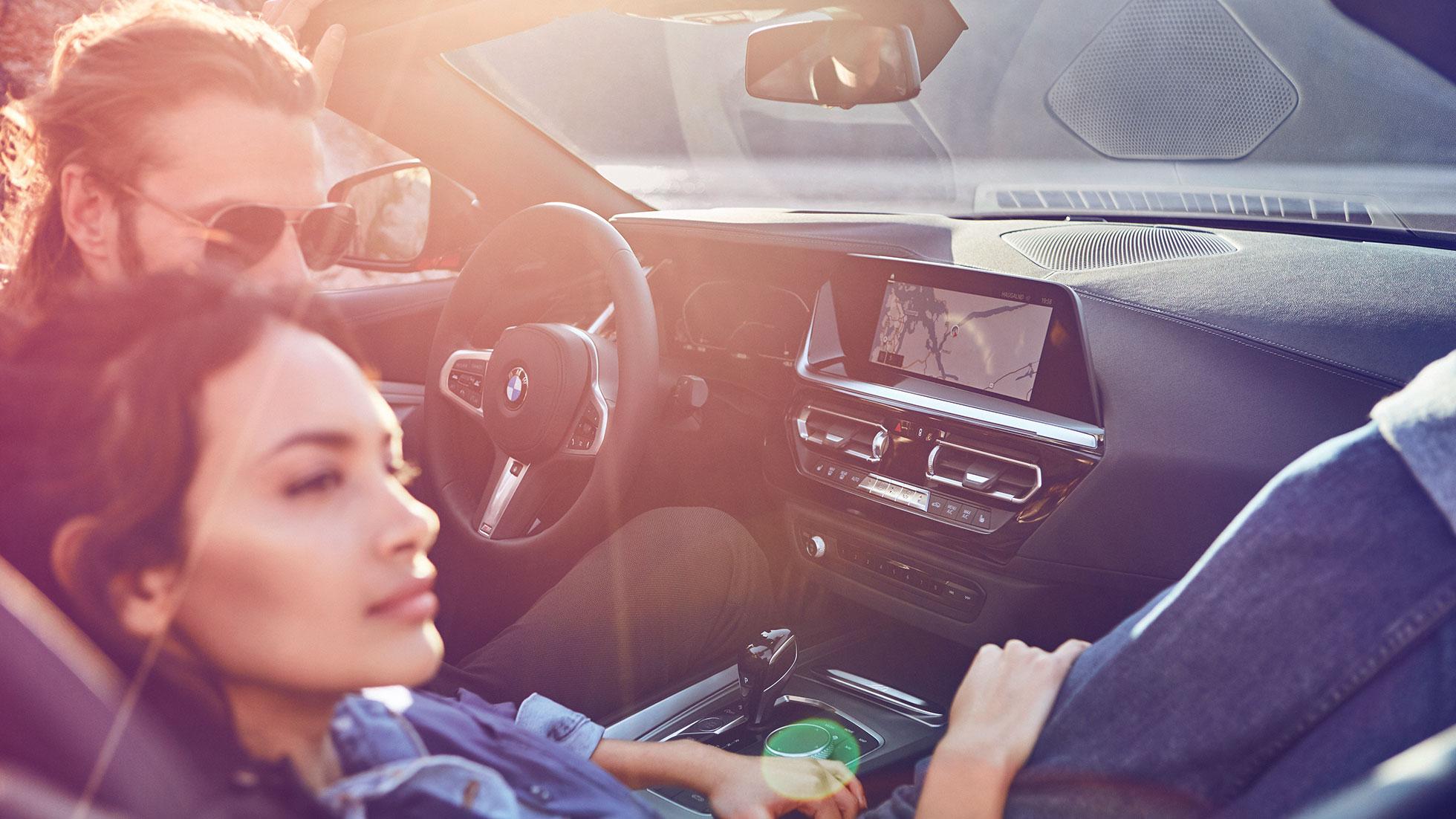 Темноволосая женщина и мужчина в BMW Z4 Roadster
