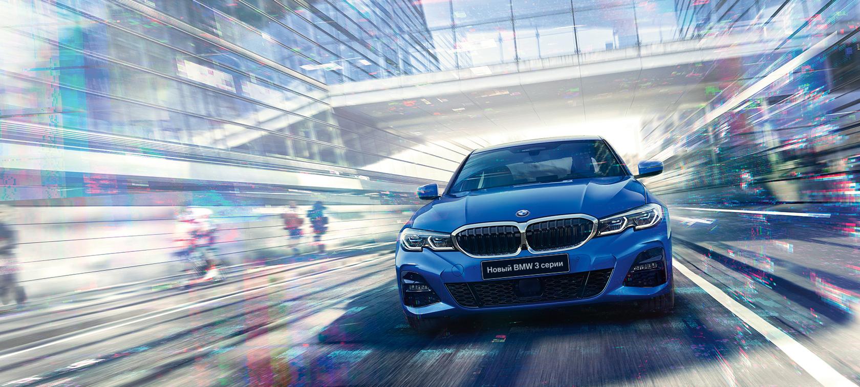 Вид спереди седана BMW 3 серии в движении в дневное время на фоне здания со стеклянным фасадом.